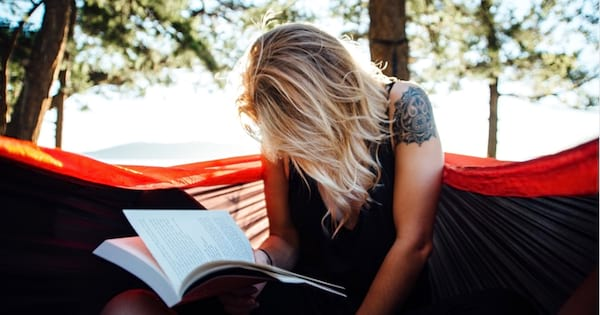 woman with blonde hair and a tattoo sitting outside in sunlight reading a book, 2018 books