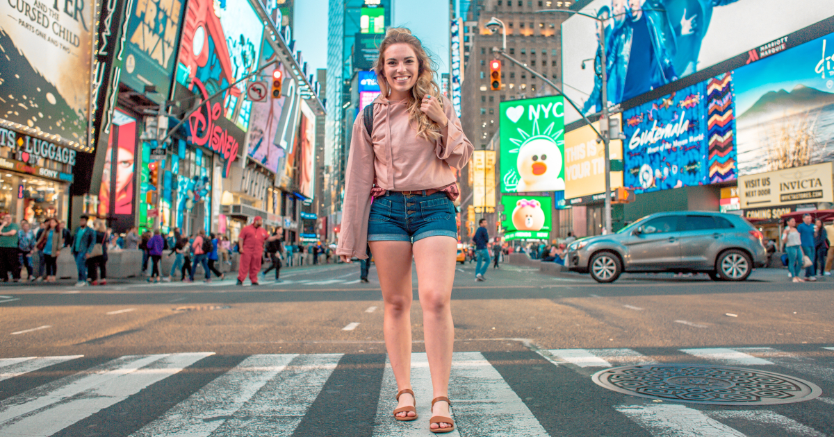 Girl standing in the middle of Times Square for a photo
