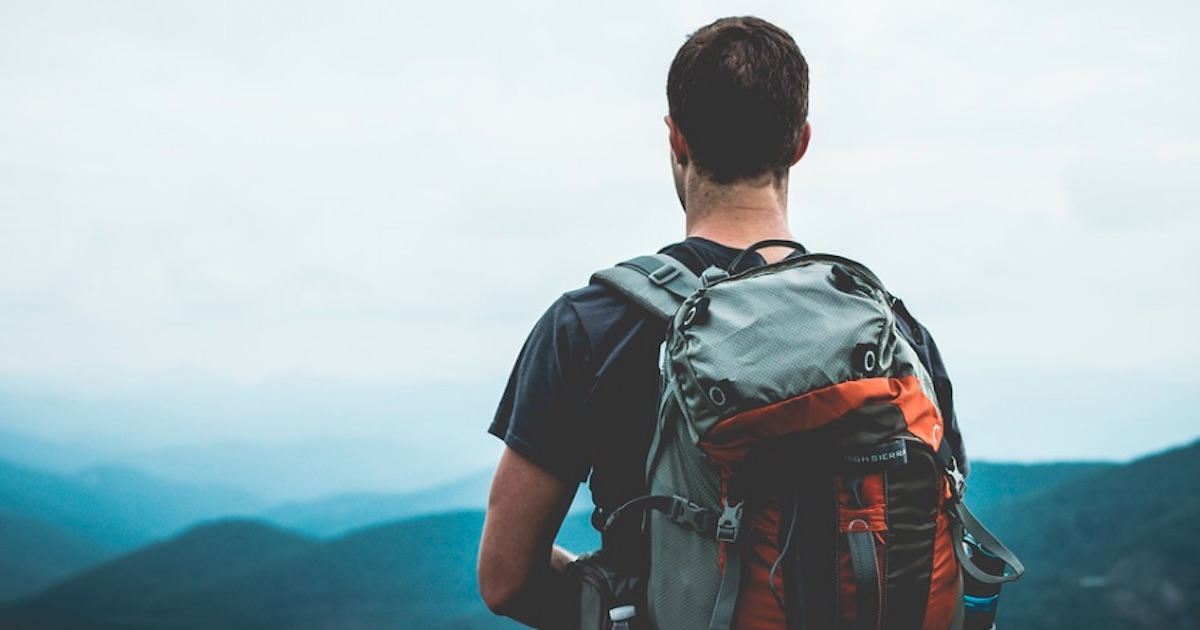man hiking with backpack looking over mountains, New Years