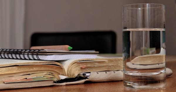 glass of water on table next to book, New Years