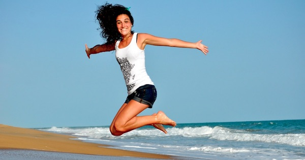 woman jumping in the air on the beach