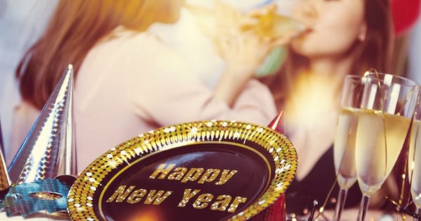 New Year's Eve Instagram Captions, closeup of a black and gold plate that says \Happy New Year\ with two women drinking champagne in the background