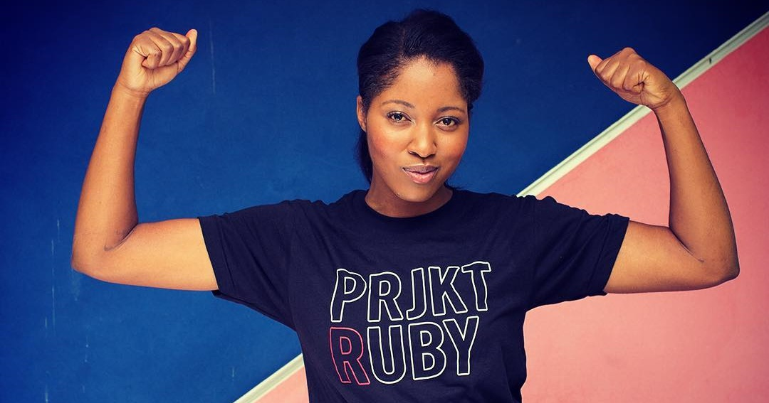 How To Order Birth Control Online, photo of a black woman with her hair tied back flexing and wearing a navy PRJKT RUBY shirt, health