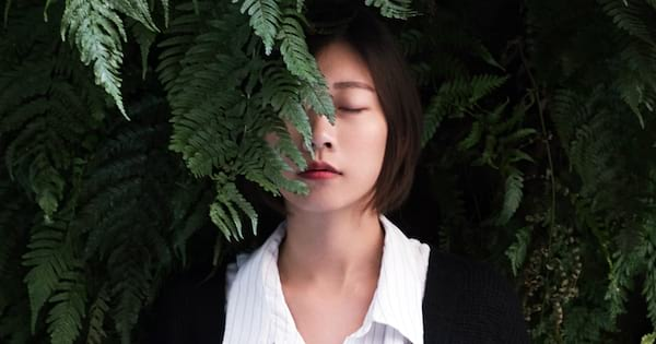 Buddhist Instagram Captions, closeup of an Asian woman with her eyes closed and a fern partially obscuring her face