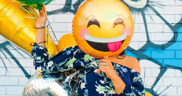 self deprecating instagram captions, woman with smile with tongue out emoji balloon in front of her face