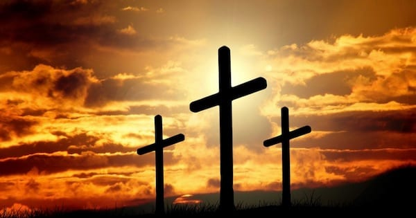 silhouette of three crosses on a hill with the sunset behind them, hymn religion
