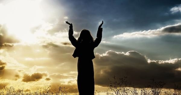silhouette of woman with arms in the air against a background of clouds and the sun, hymn religion