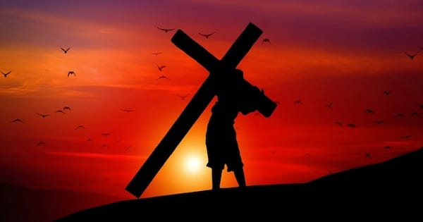 silhouette of man carrying cross on a hill against the sunset, hymn religion