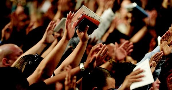 people worshipping with their hands in the air holding bible, hymn religion
