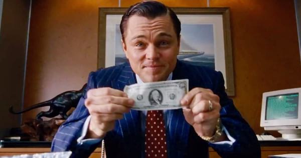 Leonardo DiCaprio holding up a $100 bill to the camera in The Wolf of Wall Street