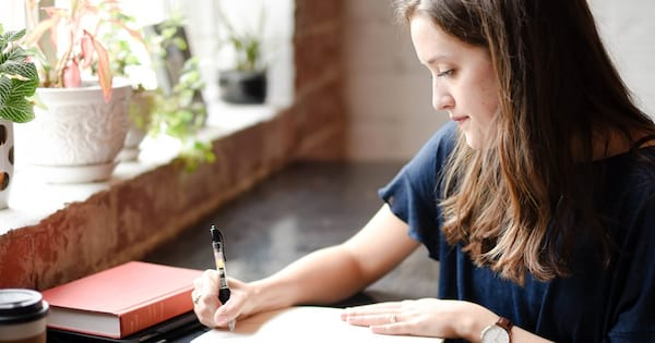 How To Start 2019 Off On the Right Foot, photo of a white woman with brown hair writes in a notebook, career, family, home