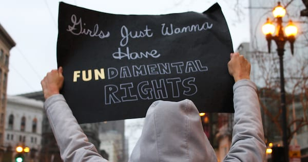 Woman holding a 'Girls Just Wanna Have Fundamental Rights' sign during the Women's March