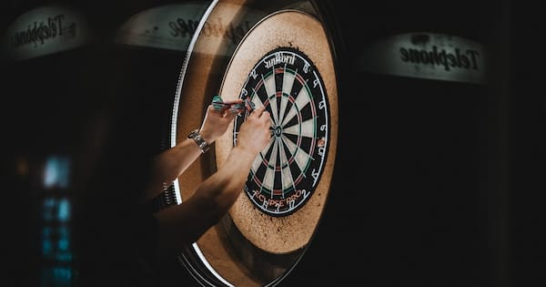 Darts Instagram Captions, closeup of a white man's hands pulling darts from a dartboard, culture