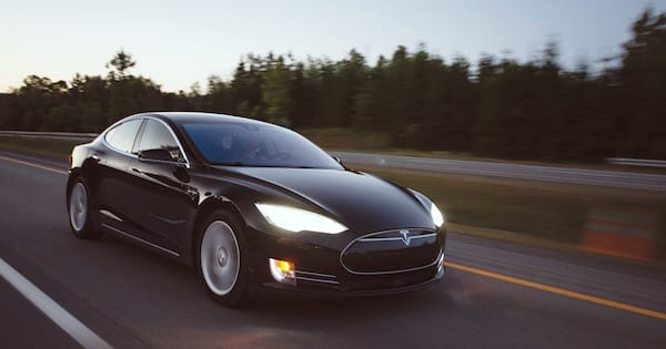 Tesla Instagram Captions, photo of a black Tesla driving down the road, culture