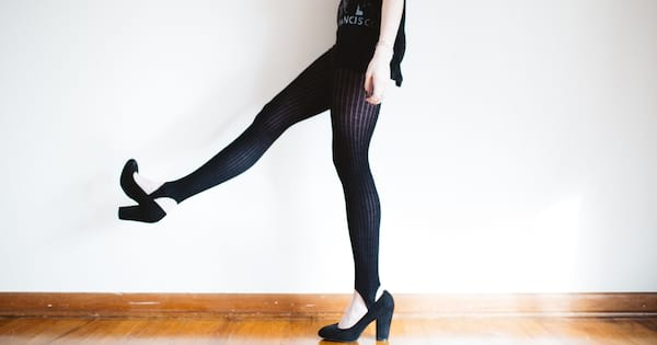 Image of a woman kicking up her black heels.