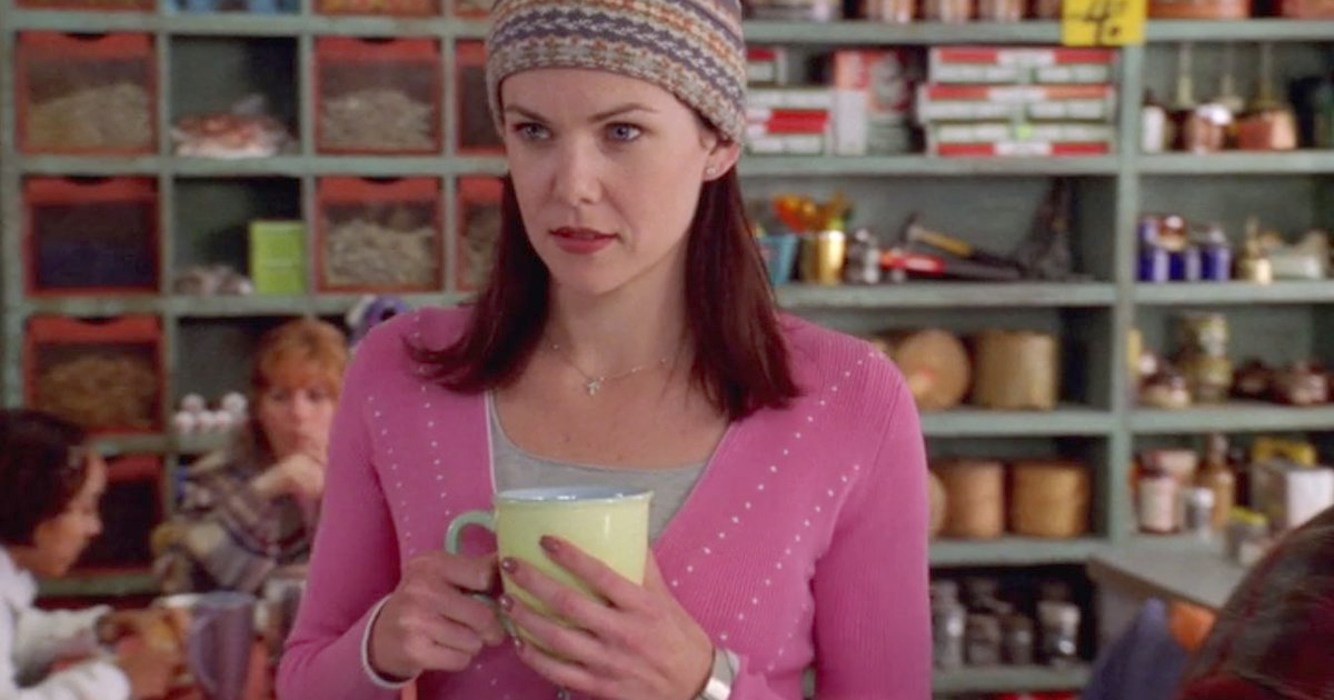 Lorelai Gilmore holding a yellow coffee mug in her hands on Gilmore Girls
