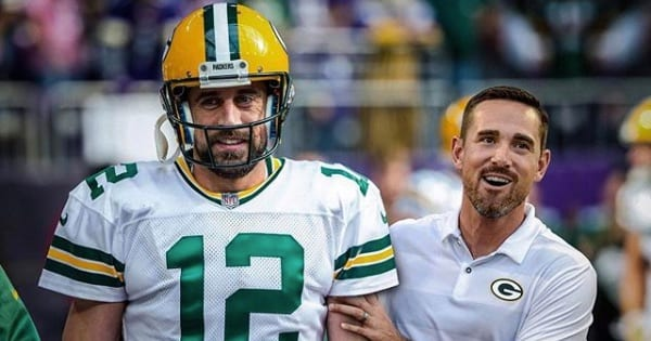 aaron rodgers quarterback of the green bay packers wearing uniform with team coach, nfl quarterback