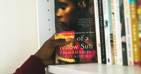 Book Club Instagram Captions, a black hand reaches for Half of a Yellow Sun by Chimamanda Ngozi Adichie, their maroon sleeve visible, books