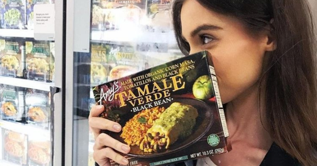 Girl holding up Amy's Tamale Verde and Black Bean frozen meal over her face