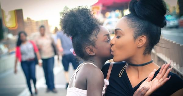 mother holding daughter and kissing her, parenting