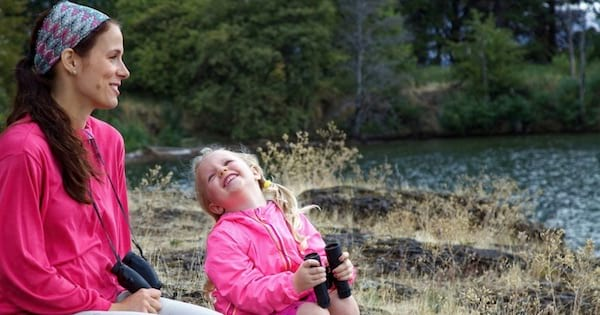 mother and daughter holding binoculars sitting outside by a lake, parenting