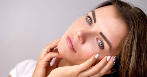 woman holding face, skincare