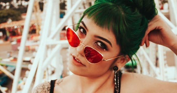 Millennial Instagram Captions, closeup of a white woman with her green hair tied back, also wearing red sunglasses and tattoos on her shoulder, culture