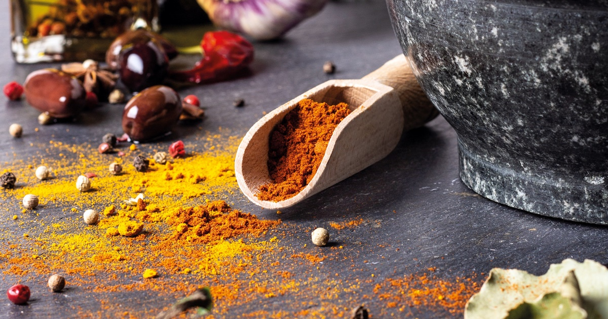 Benefits of Turmeric, image of turmeric sprinkled across the table and in a wooden scoop, health, food & drinks
