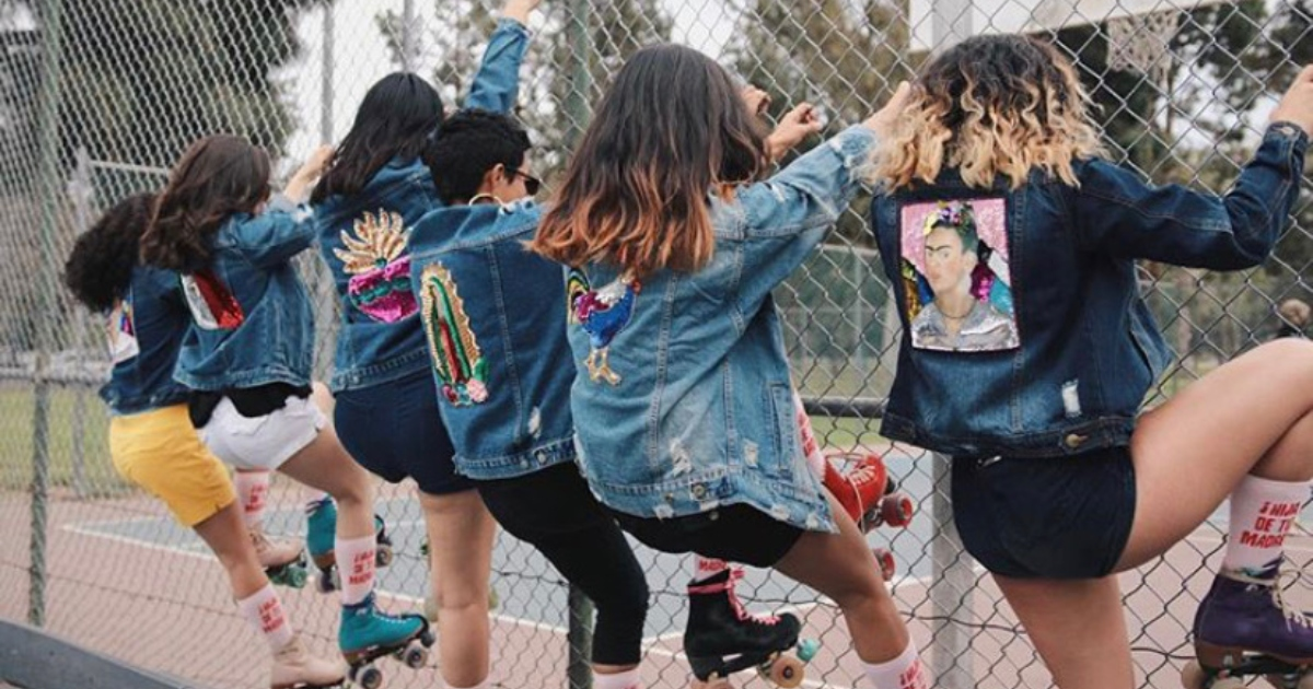 Photo of women climbing the fence with skate, wearing some merchandise from Hija De Tu Madre.