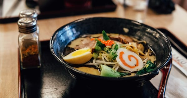 Ramen Instagram Captions, closeup of a bowl of ramen with a hard-boiled egg and veggies on top, food & drinks