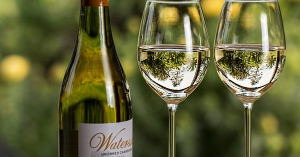 Chardonnay Instagram Captions, photo of two glasses and a bottle of chardonnay, food & drinks