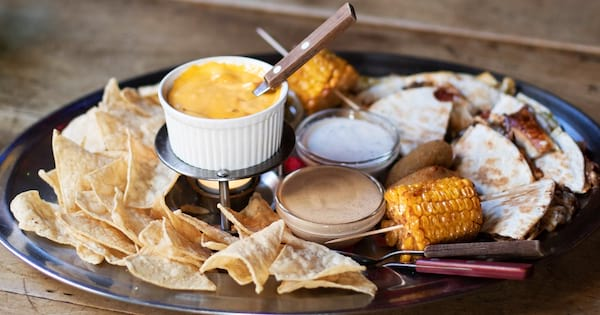 Queso Instagram Captions, photo of a plate of tortilla chips, queso, and other dips, food & drinks