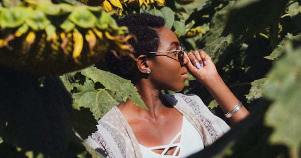 What Is Mindfulness?, photo of a black woman in profile standing in a sunflower field, she is touching her sunglasses, health, culture