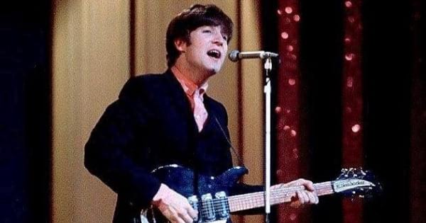 john lennon of the beatles playing guitar and singing