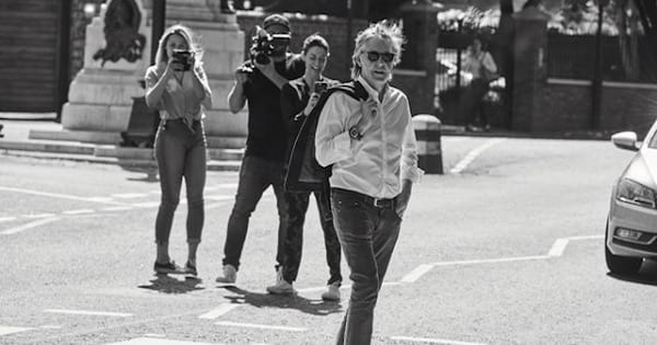 paul mccartney walking in the street with photographers behind him, the Beatles
