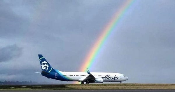 alaska airlines plane on tarmac with rainbow behind it, airline