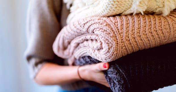 Warm But Cute Sweaters, closeup of a white woman holding a stack of folded sweaters, fashion