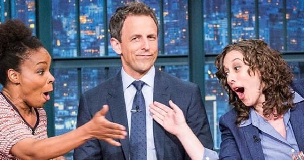 seth meyers sitting at desk with two women next to him, late-night tv host