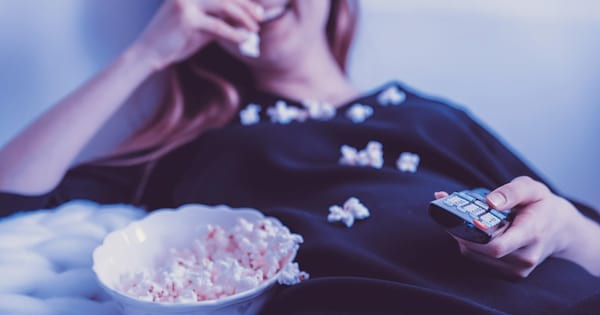 TV Shows You Won't Regret Watching, photo of a white woman slouching as she eats popcorn and holds a remote, tv, pop culture