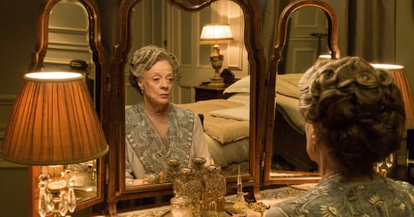 Maggie Smith sitting in front of a vanity on an episode of Downton Abbey