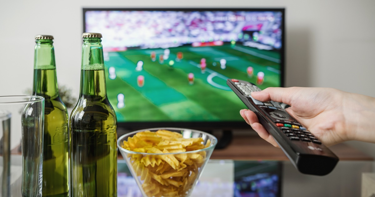 Celebrating Super Bowl Food, image of a hand holding a remote pointed at the TV with a football game on in the background, food & drinks
