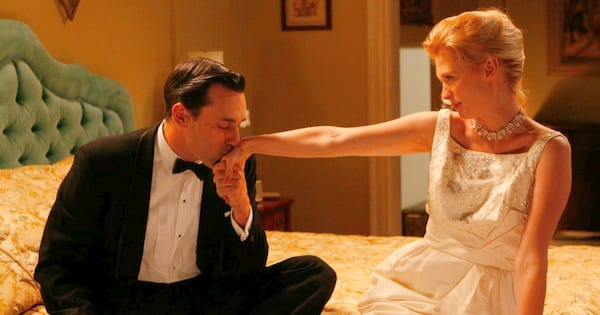Don Draper kissing Betty Draper on the hand in a hotel room after their wedding night on an episode of Mad Men