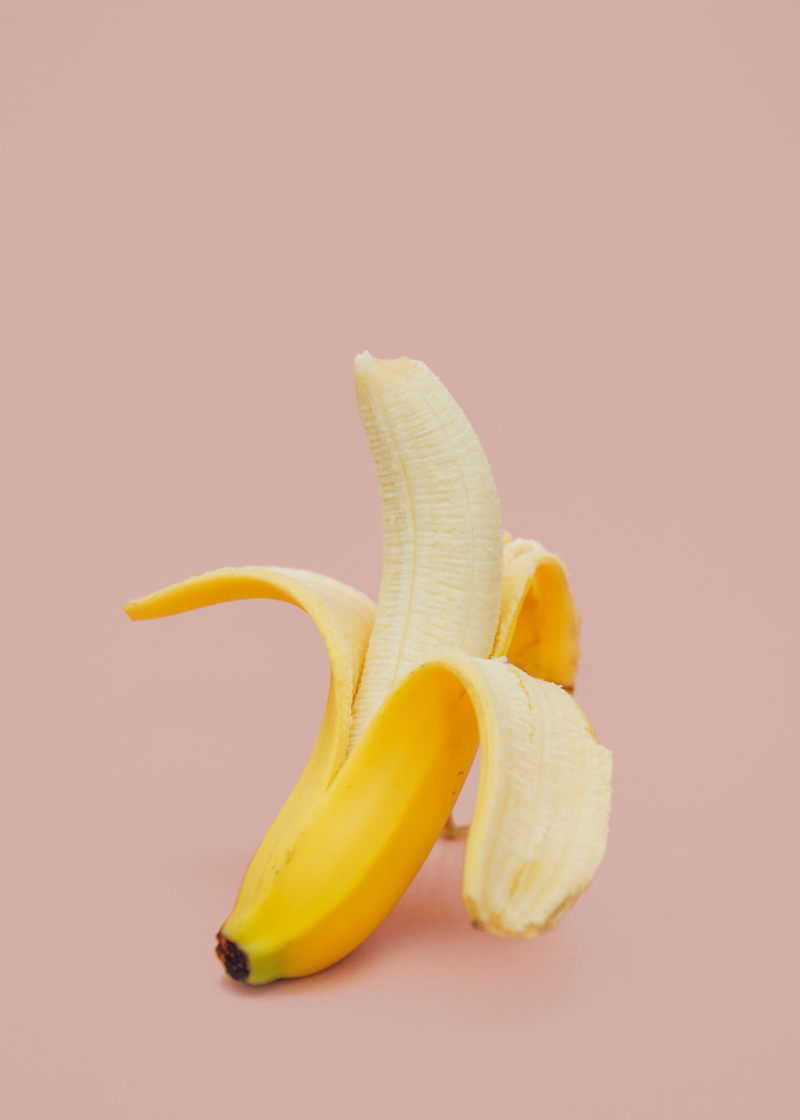 Unpeeled banana on a pink background