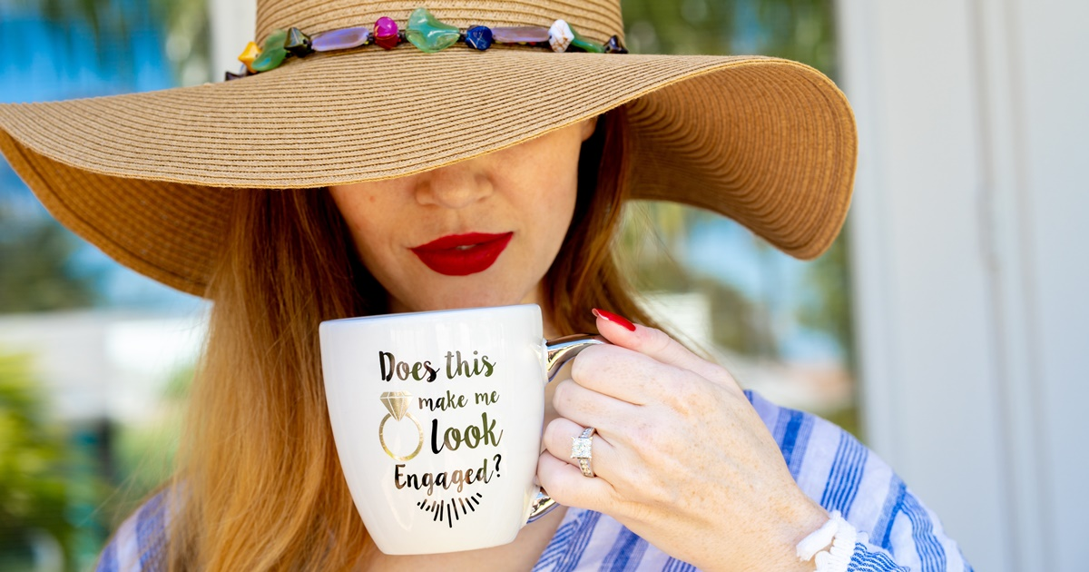 Engagement Instagram Captions, closeup of a white woman holding a mug that says \Does this ring make me look engaged?\, relationships