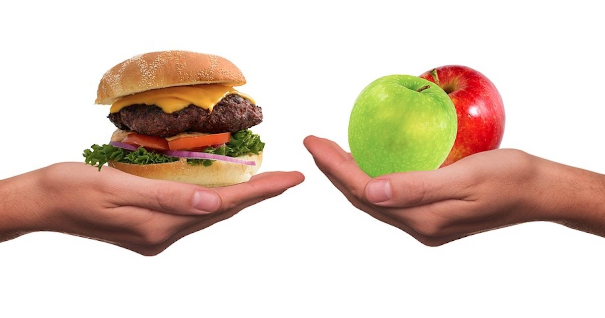hands holding our hamburger and apple, food