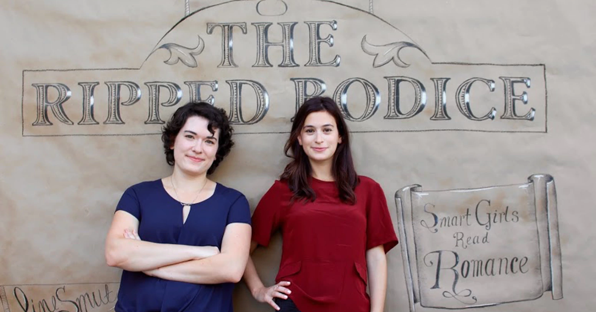 Romance Bookstore, photo of Bea and Leah Koch standing in front of a mock up of their store, The Ripped Bodice, books