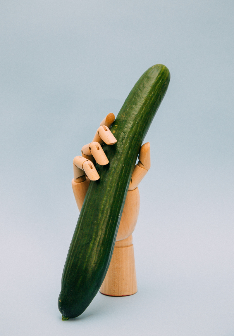 Mannequin hand giving hand job to large cucumber