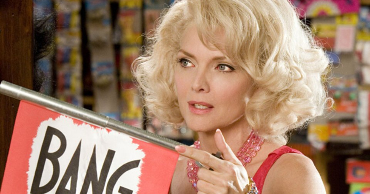 Michelle Pfeiffer as Velma Von Tussle holding a fake gun in a scene from Hairspray (2007)