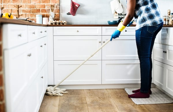 woman cleaning her kitchen floors with a mop