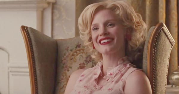 Jessica Chastain smiling and leaning back in an arm chair during a scene from The Help